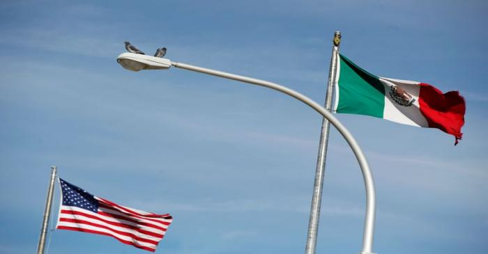FILE PHOTO: The US flag and the Mexico's flag are pictured on the international border bridge