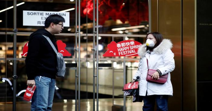 Tourist wears a protective mask as she leaves the Galeries Lafayette department store in Paris