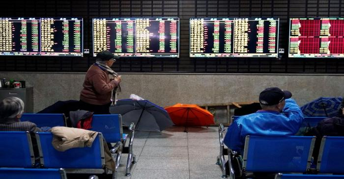 FILE PHOTO: Investors look at screens showing stock information at a brokerage house in