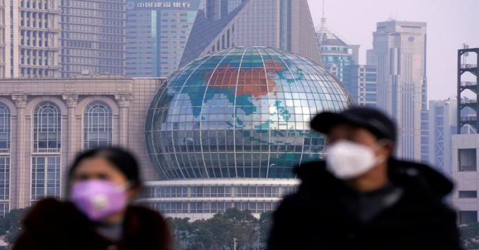 People wearing protective masks are pictured at The Bund in front of the Lujiazui financial