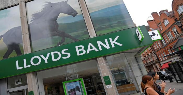 FILE PHOTO: A woman looks at her phone as she walks past a branch of Lloyds bank in London,