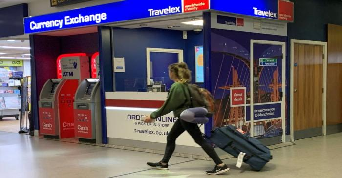FILE PHOTO: A passenger walks past a Travelex currency exchange at Manchester Airport in