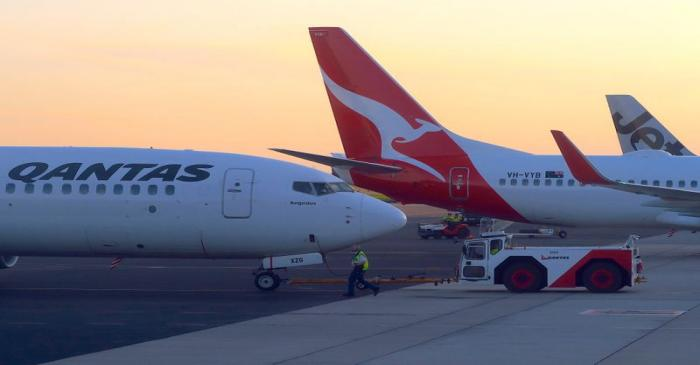 Workers are seen near Qantas Airways, Australia's national carrier, Boeing 737-800 aircraft on