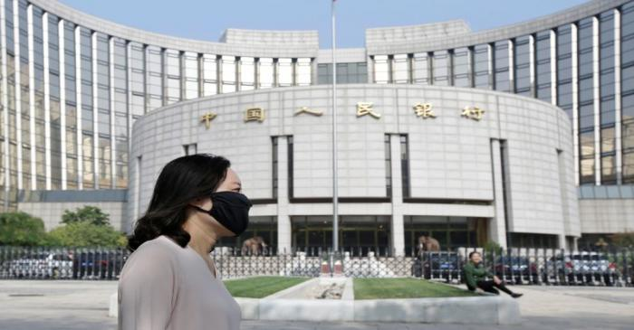 A woman walks past the headquarters of the PBOC, the central bank, in Beijing