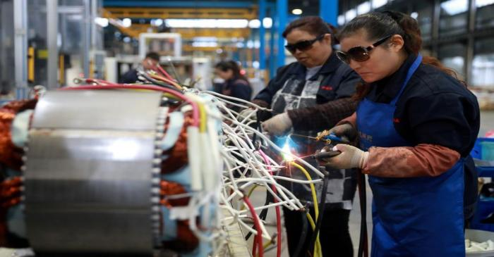Women wearing sunglasses work at a production line manufacturing electric machine parts at a