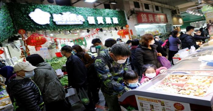 FILE PHOTO:  Customers wear masks as they are buying foods at a food market, in Hong Kong