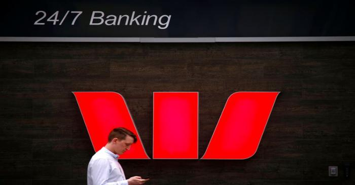 A pedestrian looks at his phone as he walks past a logo for Australia's Westpac Banking Corp