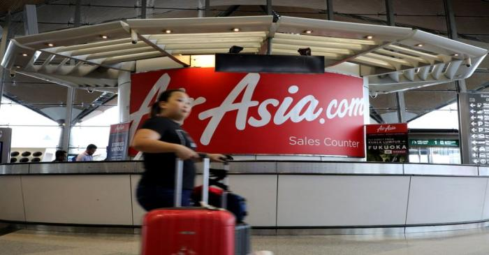 FILE PHOTO:  A woman walks past an AirAsia counter at Kuala Lumpur International Airport in