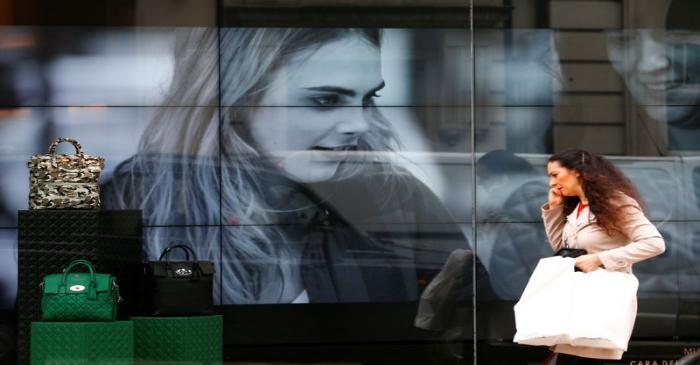 FILE PHOTO: A woman walks past a video display in the shop window of a Mulberry store in