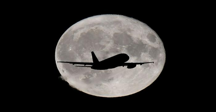 A passenger plane passes in front of the full moon as it makes it's final landing approach to