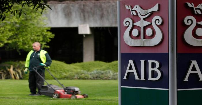 FILE PHOTO:  A gardener mows the grass outside the headquarters of AIB on the day the bank