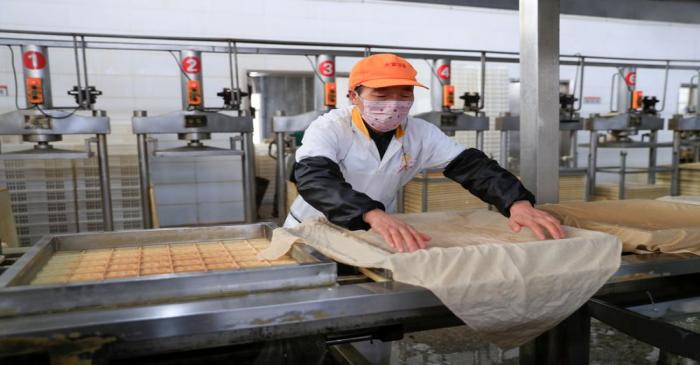 Worker wearing a face mask works on a production line manufacturing soybean-based food products
