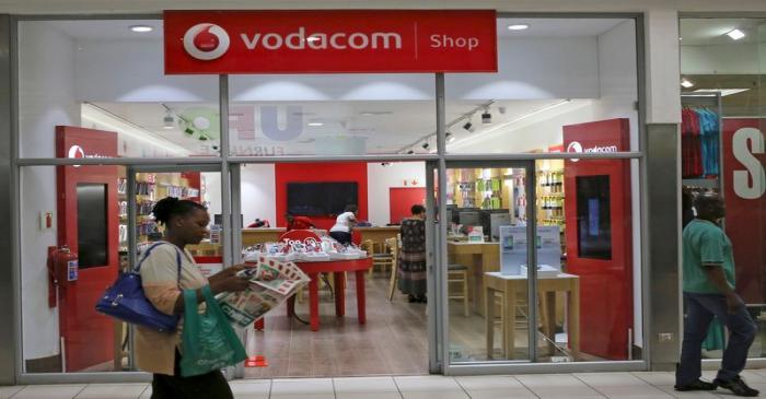 A shopper walks past a Vodacom shop in Johannesburg