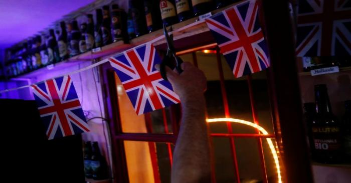 British resident Paul Darwent cuts a cord with British flags inside his bar after the countdown