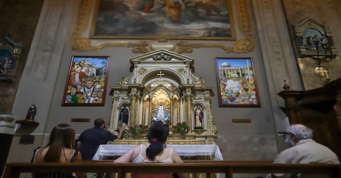 People sit in pews at Pope Francis' old church the Basilica San Jose de Flores, in the district