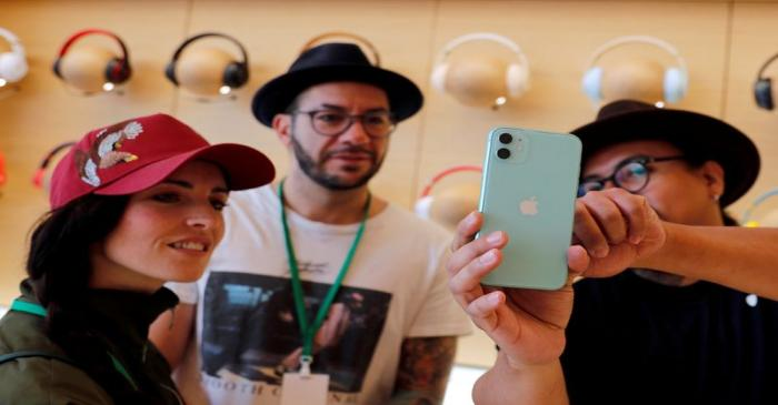 FILE PHOTO: People look at an app on the new iPhone inside the new Apple Store in Mexico City