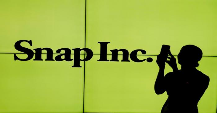 FILE PHOTO: A woman stands in front of the logo of Snap Inc. on the floor of the New York Stock