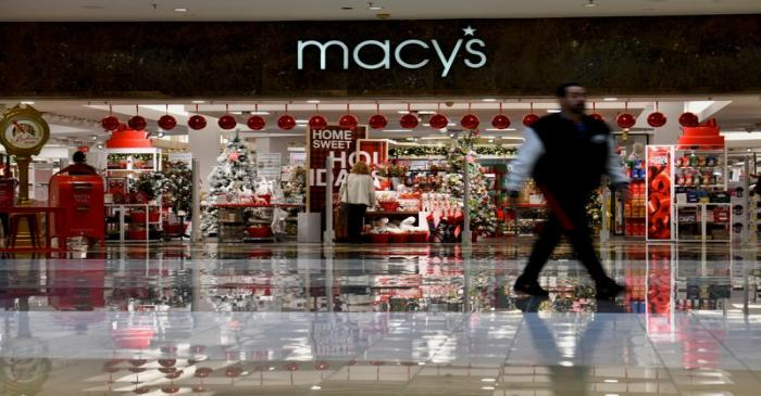Shoppers walk past a Macy's storefront display as holiday shopping accelerates at the King of