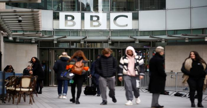 Pedestrians walk past a BBC logo at Broadcasting House, as the corporation announced it will