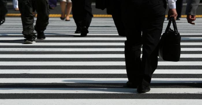 Pedestrians cross a road at Tokyo's business district