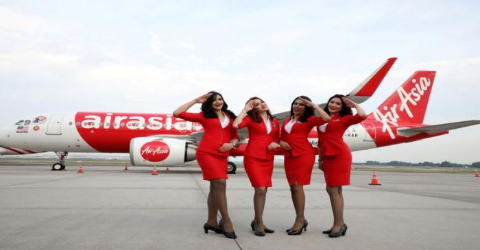 FILE PHOTO: AirAsia crew members pose for a photograph in front of an Airbus A320 plane at