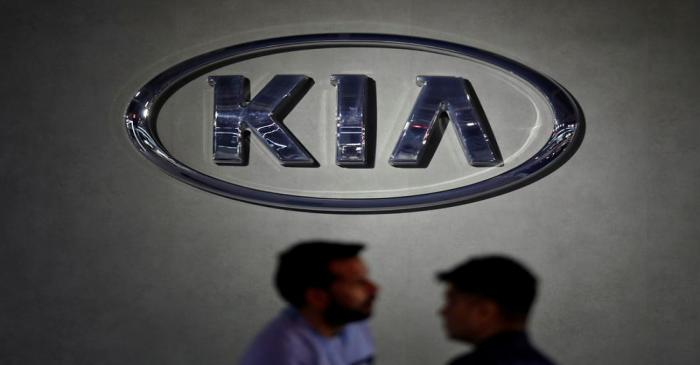 Visitors walk past the logo of Kia Motors at its pavilion at the India Auto Expo 2020 in