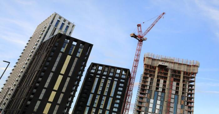 A crane is seen above some high rise building construction works at Lewisham, in London