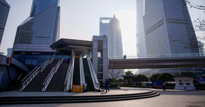 FILE PHOTO: People wearing masks are seen at Lujiazui financial district in Pudong, Shanghai
