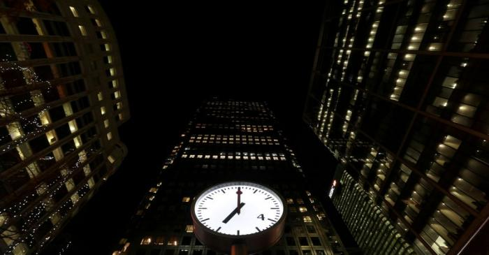 FILE PHOTO: Clocks in London's Canary Wharf financial centre strike 07:00 GMT, marking the time
