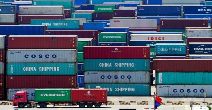 FILE PHOTO: Truck carrying containers are seen near a Chinese flag at the Yangshan Deep Water