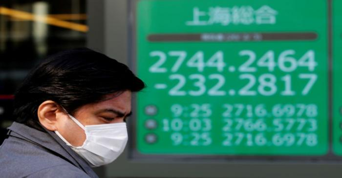 FILE PHOTO:  A man wearing a surgical mask stands in front of a screen showing Shanghai