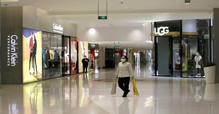 FILE PHOTO: Cleaner wearing a mask walks at a shopping mall in Beijing's central business area
