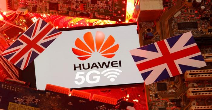 The British flag and a smartphone with a Huawei and 5G network logo are seen on a PC
