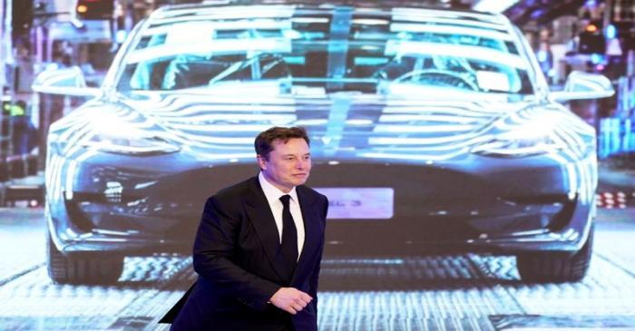 Tesla Inc CEO Elon Musk walks next to a screen showing an image of Tesla Model 3 car during an