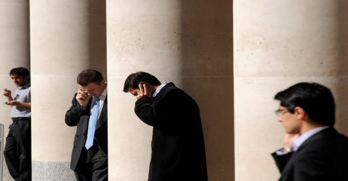 City workers make phone calls outside the London Stock Exchange in Paternoster Square in the