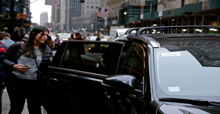 FILE PHOTO: A passenger enters an Uber car in New York City