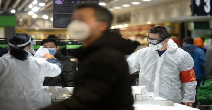 Customers wearing face masks shop inside a supermarket following an outbreak of the novel