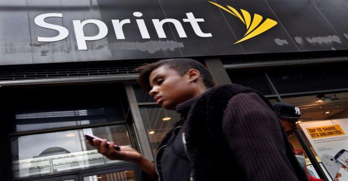 FILE PHOTO: A woman uses her phone as she walks past a Sprint store in New York's financial