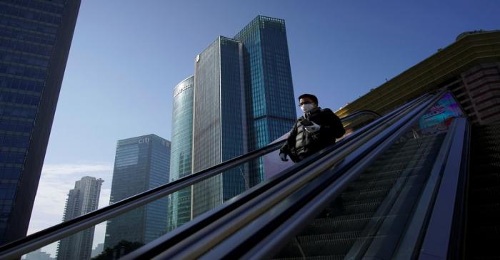 A man wearing a face mask rides an escalator at the Lujiazui financial district in the morning