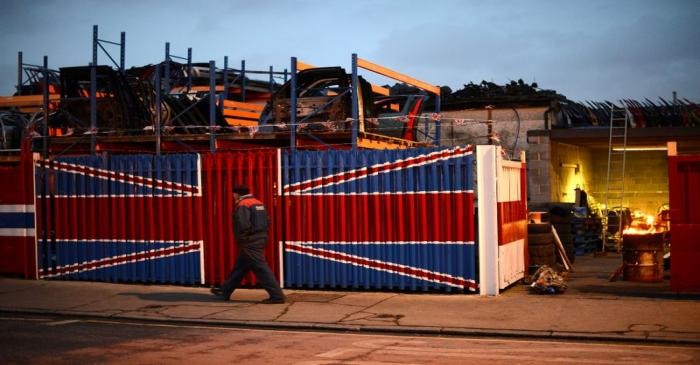 A man walks past a car scrap yard in east London