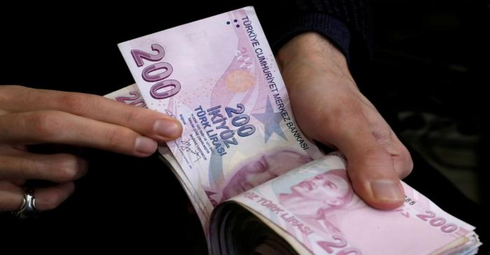 FILE PHOTO: A merchant counts Turkish lira banknotes at the Grand Bazaar in Istanbul