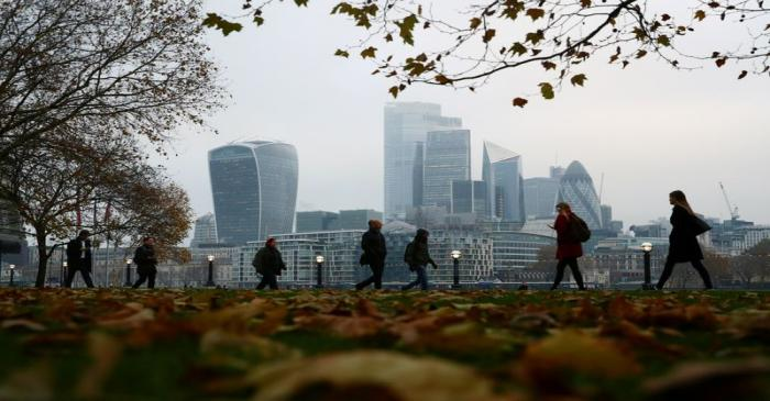 FILE PHOTO: People walk through autumnal leaves in front of the financial district in London