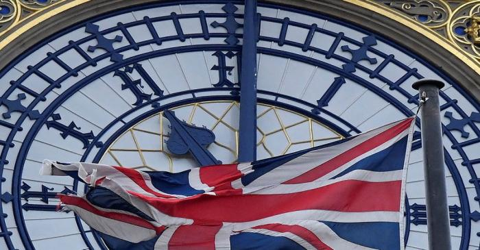 The British union flag is seen fluttering as the clock face of Big Ben shows eleven o'clock,
