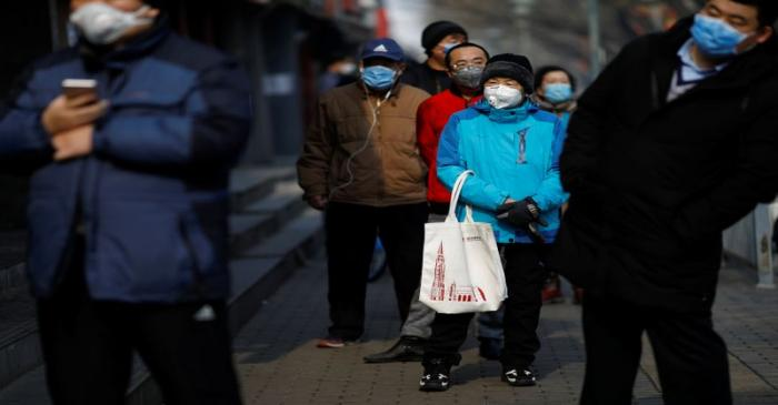 Customers wearing face masks queue for food outside a store, as the country is hit by an