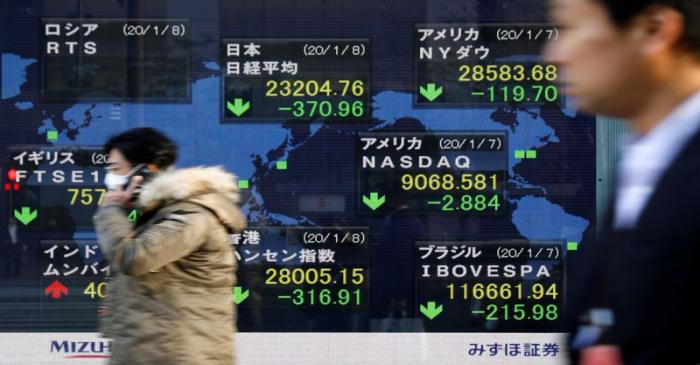 People walk past an electronic display showing world markets indices outside a brokerage in