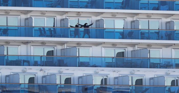 FILE PHOTO: A passenger stretches on the balcony of a cabin of the cruise ship Diamond
