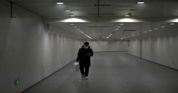 FILE PHOTO: Man wearing a face mask walks in a subway station, following an outbreak of the