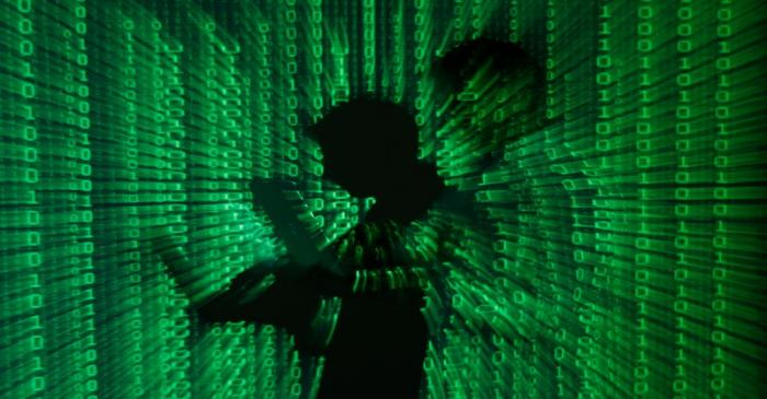An illustration picture shows projection of binary code on man holding aptop computer in Warsaw