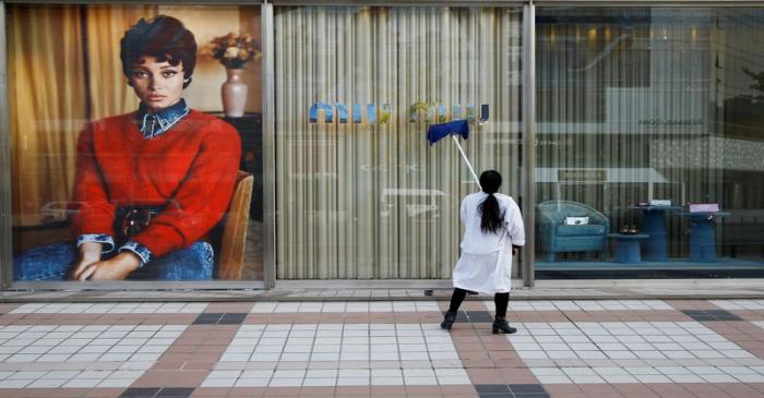 FILE PHOTO: A woman cleans the shop window of a boutique of the Italian high fashion brand Miu