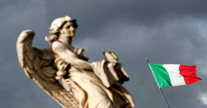 FILE PHOTO: An Italian flag waves behind a statue near Ponte Sant'Angelo in Rome